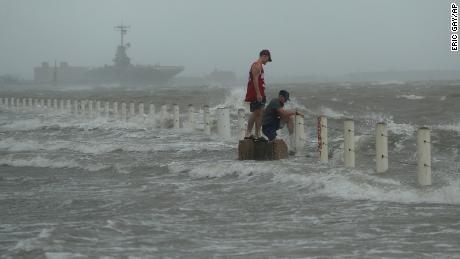 Dos hombres se paran cerca de un malecón mientras el huracán Hanna toca tierra.
