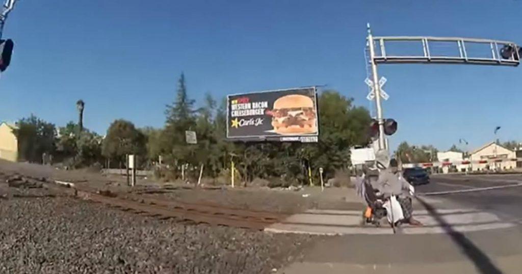 El video muestra a un oficial de policía sacando a un hombre en silla de ruedas de las vías del tren antes de que llegue el tren.