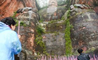 Turistas queman ofrendas a los pies del Buda Gigante en 2016