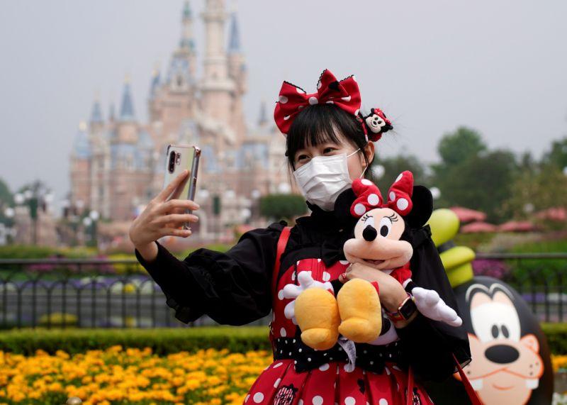 Un visitante vestido como un personaje de Disney se toma una selfie mientras usa una máscara facial protectora en el Shanghai Disney Resort cuando el parque temático Shanghai Disneyland reabre después de un cierre debido al brote de la enfermedad del coronavirus (COVID-19), en Shanghai, China, 11 de mayo de 2020 REUTERS / Aly Song IMÁGENES TPX DEL DÍA